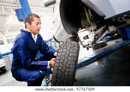 Mechanic placing a wheel back into a car