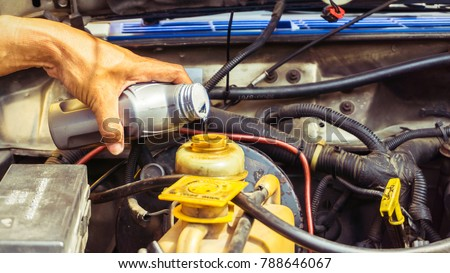 Mechanic  pouring Brake fluid to brake oil tank in service shop #788646067