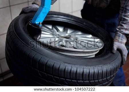Mechanic removes  car tire closeup
