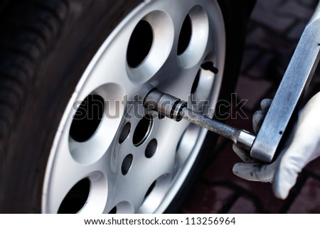 Mechanic repair wheel with wrench - stock photo