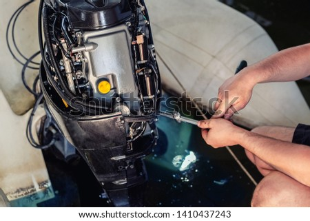 mechanic repairing inflatable motorboat engine at boat garage. Ship engine seasonal service and maintenance. Vessel motor with open cover #1410437243