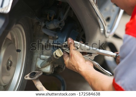 mechanic repairing motorbike holding adjustable wrench