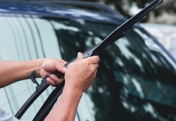 Mechanic replace windshield wipers on car. Replacing wiper bladesChange cars wiper blades. Technician Man changing windshield wipers blades on car.