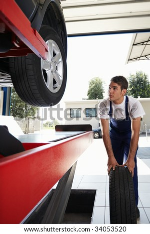 mechanic replacing car tyre in auto repair shop. Front view
