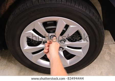 Mechanic replacing lug nuts by hand while changing tires on a vehicle.
