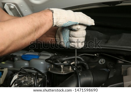 mechanic's hands in clean gloves are repairing a car. mechanic unscrews a bolt by screwdriver in a car engine close up #1471598690
