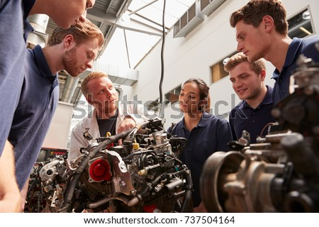 Mechanic showing engines to apprentices, low angle Foto stock ©