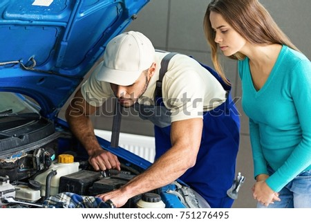 Mechanic Showing to a Woman the Engine of her Car