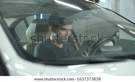 Mechanic sits in a car and looks at something on a tablet
