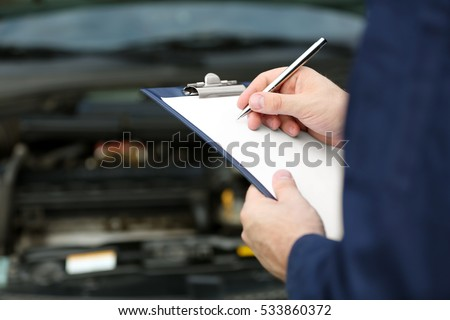 Mechanic standing in front of an open car hood with clipboard and pen. Closeup