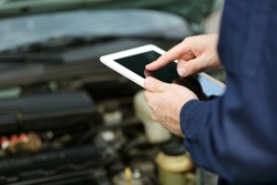 Mechanic standing in front of an open car hood with the tablet