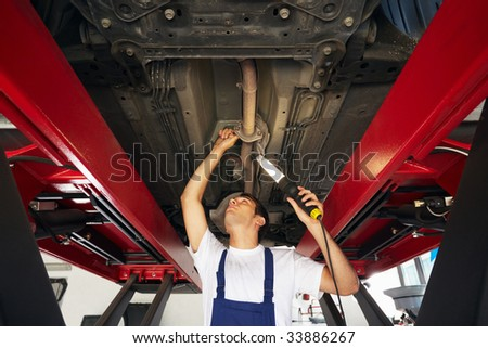 mechanic standing under car engine and holding lamp. Copy space
