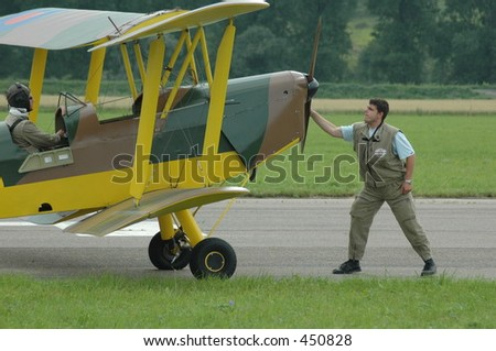 mechanic starting biplane by hand rotate propeller
