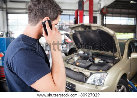 Mechanic talking on cell phone in garage