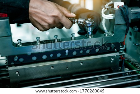 Mechanic technician hand fixing industrial machinery in factory. Technician service and maintenance packing machine equipment. Worker use wrench maintenance industrial machinery in plant.