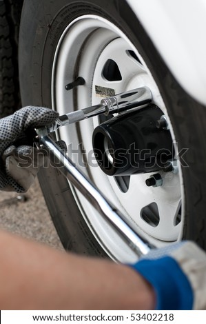Mechanic using a torque wrench socket and extension on the lug nuts of a truck wheel.