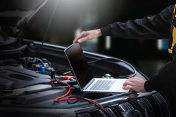 Mechanic using computer for diagnostics engine. Repairing car. Blur garage auto repair service in background.