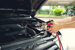 Mechanic using jumper cables to start-up a car engine