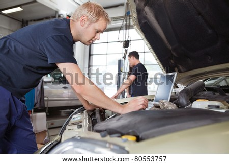 Mechanic using laptop while working on car with people in background
