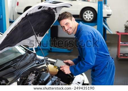 Mechanic using tablet to fix car at the repair garage #249435190