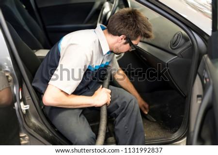 mechanic vacuuming the car at the garage #1131992837