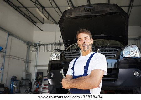 Mechanic with arms folded  in auto repair shop.