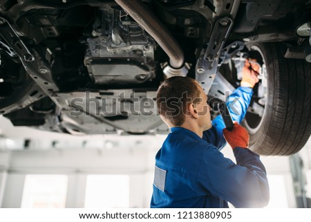 Mechanic with lamp checks car brake hoses