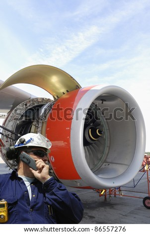 mechanic with large jet engine in background, airport maintenance works
