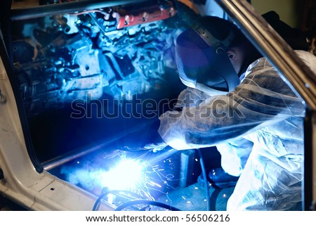 mechanic with protective mask welding car body