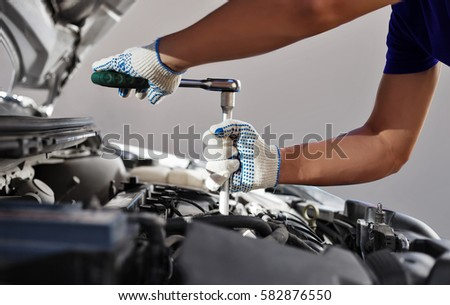 Mechanic working in auto repair garage. Car maintenance #582876550