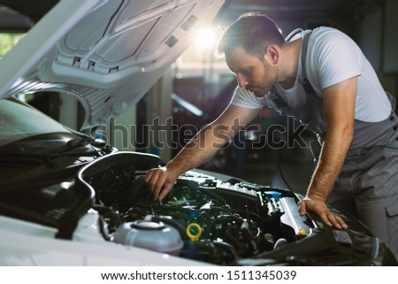Mechanic working on a car in auto repair shop #1511345039