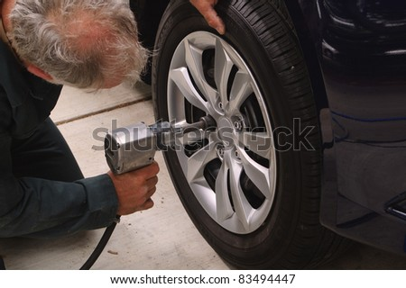 Mechanic working on car using an air impact tool to change tires on a vehicle.