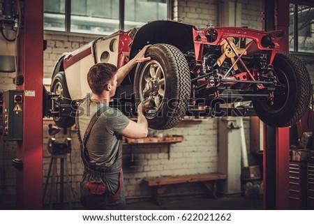 mechanic working on classic car ...