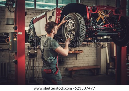 mechanic working on classic car ...