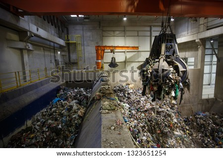 Mechanical claw hand grabbing pile of mixed waste, deposited in the waste treatment plant depot, separation and treatment. Waste disposal, management, reuse, recycle and recovery concept.