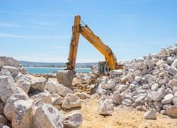 Mechanical excavator working on coast with stones.