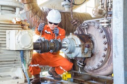 Mechanical inspector inspection and re-alignment oil pump centrifugal type and electric motor. Offshore oil and gas industry maintenance activities.