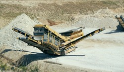 Mechanical machine, conveyor belt for transporting and crushing stone with sand. Mining quarry for the production of crushed stone, sand and gravel for use in the construction industry.