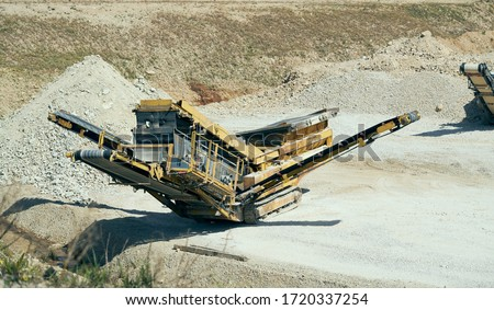 Mechanical machine, conveyor belt for transporting and crushing stone with sand. Mining quarry for the production of crushed stone, sand and gravel for use in the construction industry. Foto stock ©