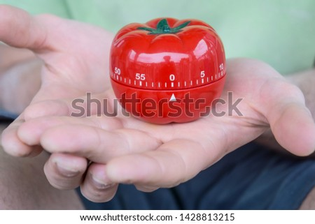 Mechanical red tomato kitchen timer set to 0, held by a person's both hands, with open palms. Old school productivity tool for time management and procrastination. #1428813215