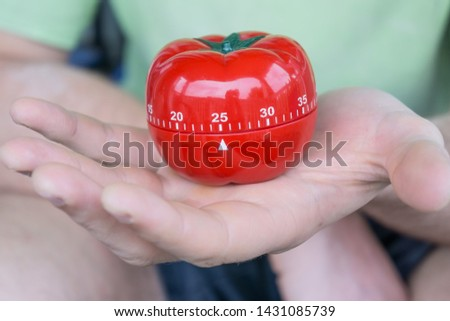 Mechanical red tomato kitchen timer set to 25 minutes, held by a person with one open hand. Old school productivity tool for time management and procrastination.