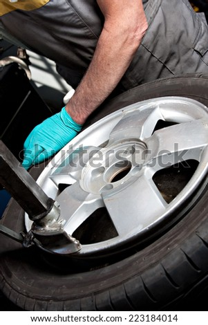 Mechanical repairs a tire in the garage.