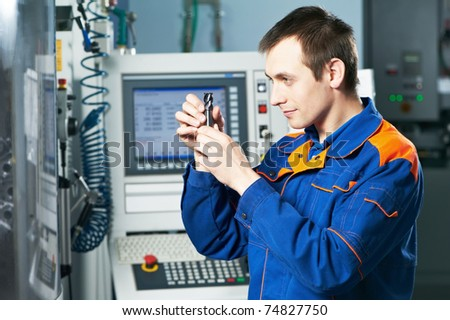 mechanical technician checking cutting detail after cnc milling machine center at tool workshop