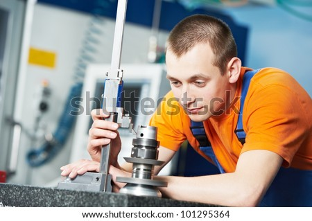 mechanical technician measuring cutting tool before cnc milling machine center at tool workshop