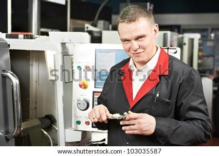 mechanical technician worker measuring detail tool after processing on cutting machine center at workshop with sliding caliper