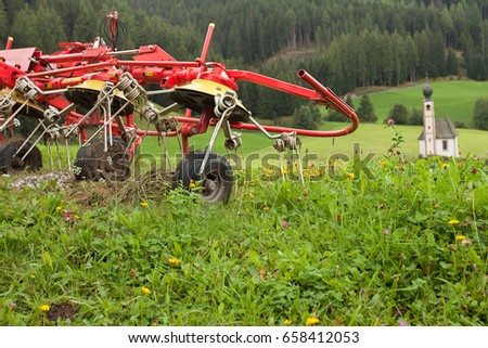 Mechanical tool used by the farmer to move the hay on the meadow, during the sunny days #658412053