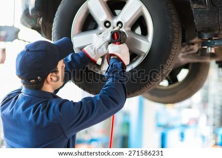 Shutterstock Mechanician changing car wheel in auto repair shop