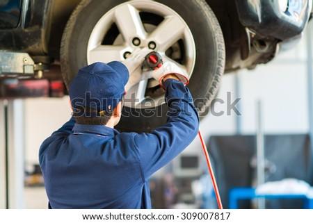 Mechanician changing car wheel in auto repair shop