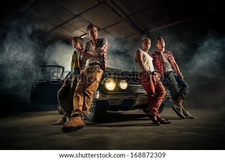 Mechanics at a garage repairing the retro car in smoke
