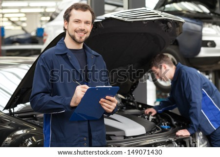 Mechanics at repair shop Cheerful young mechanic writing something in his clipboard while another one fixing a car on the background